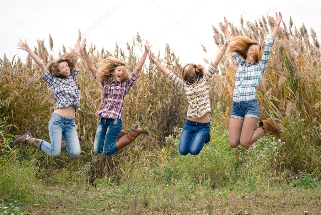 friends girls jumping high in blue sky