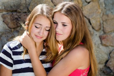 Teenage girl comforting crying friend with warm hug