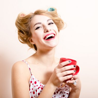 Beautiful blond funny pinup green eyes blond woman with curlers happy smiling looking at camera drinking tea & having fun