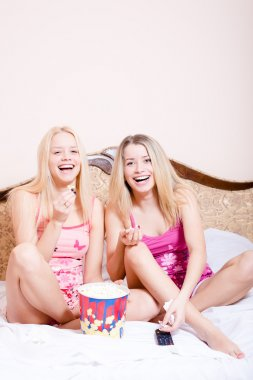 Women sitting in bed with popcorn, watching movie