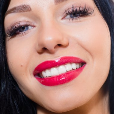 beautiful tempting brunette young woman with blue eyes, long lashes, red lipstick, happy smiling & looking at camera closeup portrait