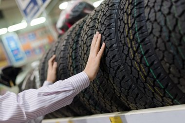 Man holding a tire in the store