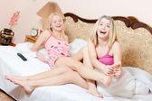 Fotografia trattamento di massaggio plantare gioiosa: belli biondi ragazza amici divertimento rilassante mentre la sorella minore rendendo piedi massaggio sorella maggiore su un bianco letto ridendo felici guardando della fotocamera