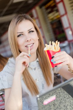 Closeup portrait on eating french fries in fast food coffee shop or restaurant beautiful blond young woman with green eyes having fun relaxing happy smiling & looking into the camera