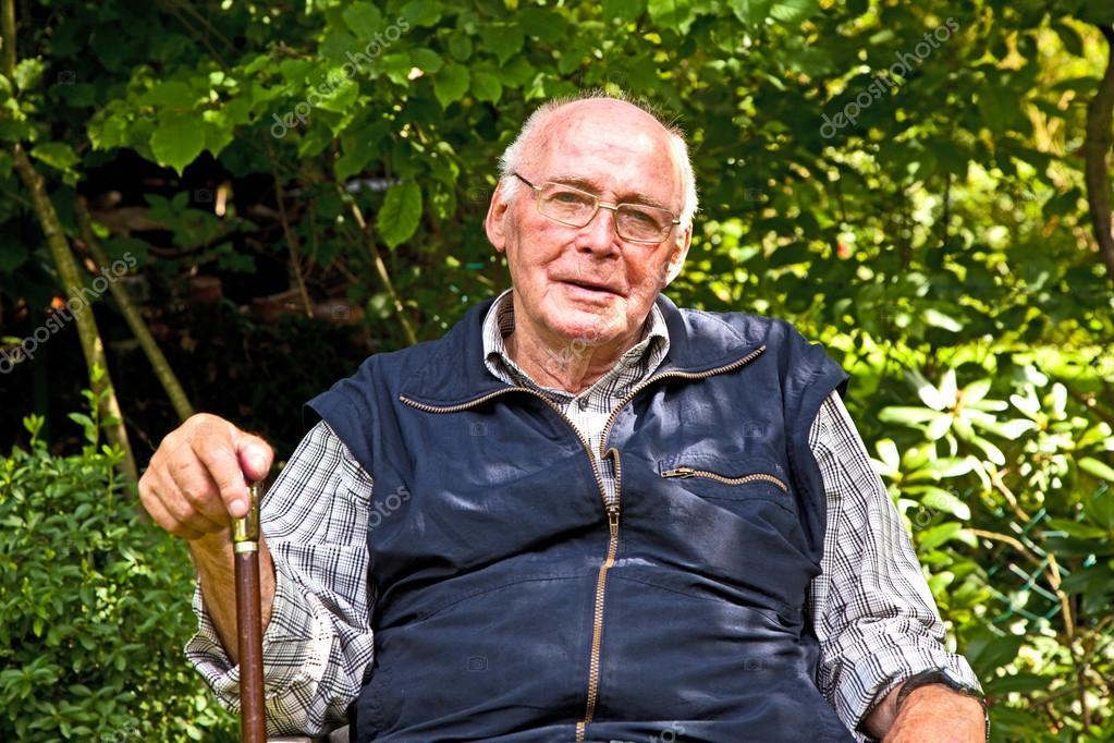 portrait of elderly man sitting happy in his garden