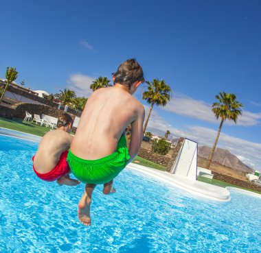 Boy jumping in the blue pool