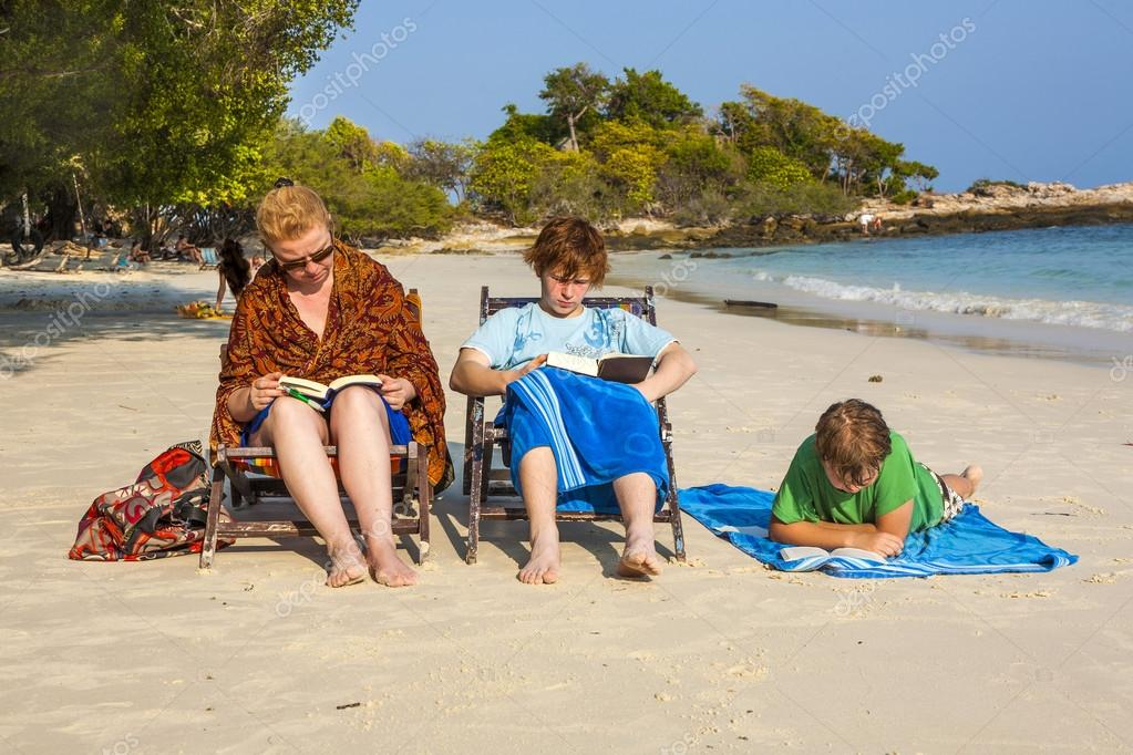 family is enjoying the sun and relaxing and reading books at the