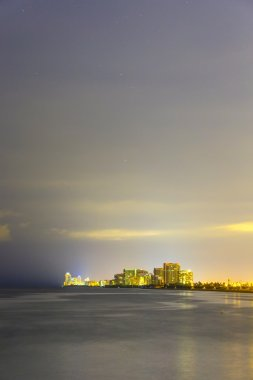 skyline of Miami sunny isles by night with reflections at the oc