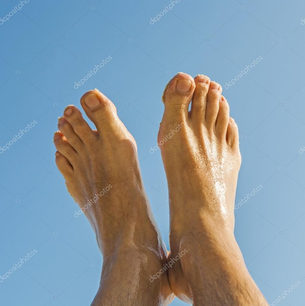 leg and feet of a man under blue sky