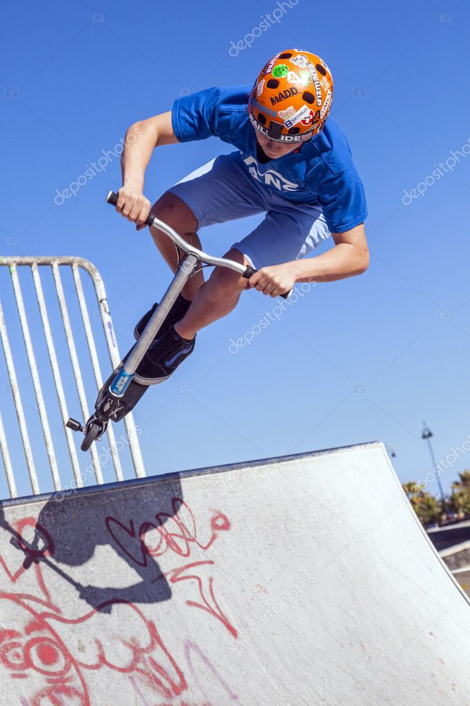 boy jumps with his scooter over a ramp