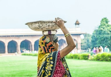 indian female worker carry stones at her heat