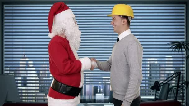 Santa claus a mladý architekt v moderní kanceláři, třesoucí se ruce a při pohledu na fotoaparát