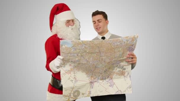 Santa claus s mladý podnikatel, čtení mapy, proti bílé