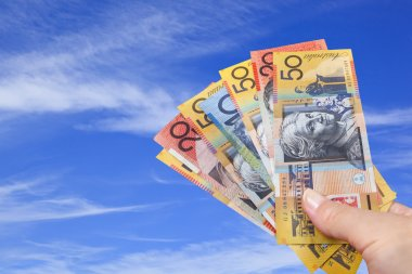 Handful of Australian Money over Blue Sky.