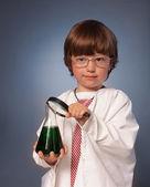 Junge Studium eines Stoffes in ein Reagenzglas mit einer Lupe