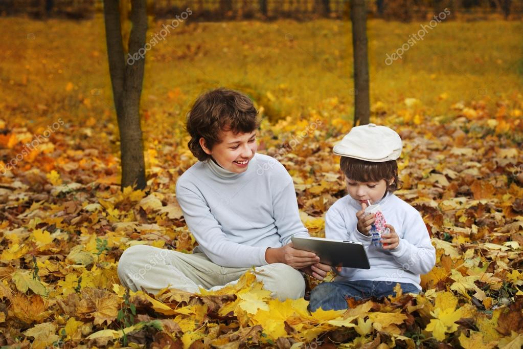 happy boys in the park using a tablet PC