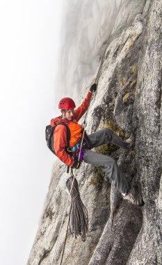 Climber rappells down a cliff.