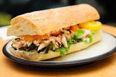 a delicious bbq chicken sandwich on french bread with tomatoes a