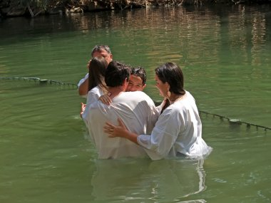 Israel Happy family after a baptism of the child in holy waters of the Jordan River