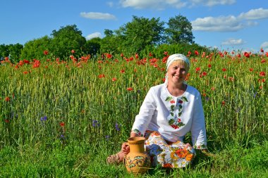The rural woman sits with a jug in a poppy field