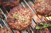 Jídlo maso - hovězí hamburgery na grilu bbq gril s plamenem