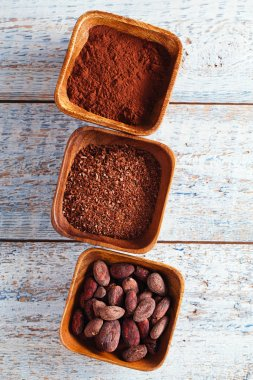 cocoa beans, powder and grated chocolate in wooden bowls, white