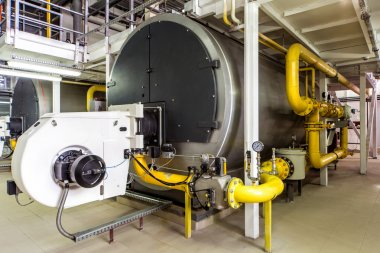 interior gas boiler room with large boilers and burners