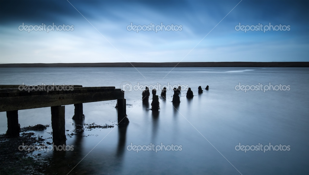Фотообои Long exposure landscape of old derelict jetty extending into lak