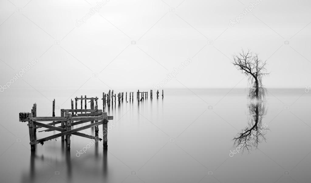 Fine art landscape image of derelict pier in milky long exposure