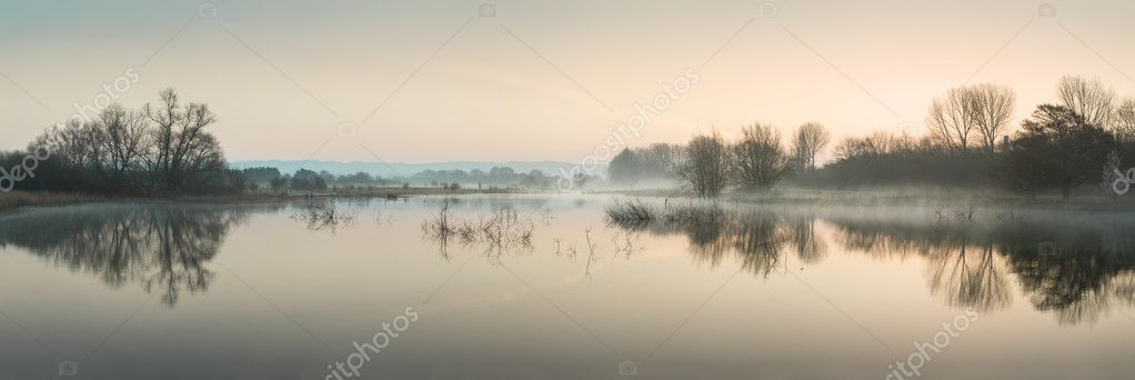 Stuning tranquil landscape panorama of lake in mist