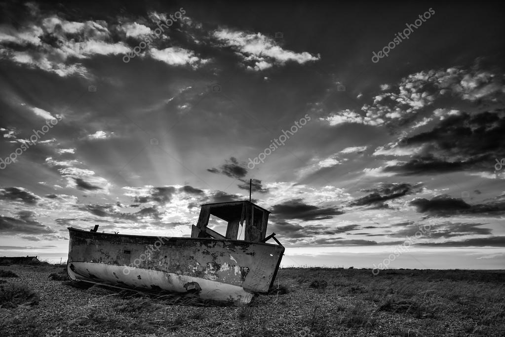 Abandoned fishing boat on beach black and white landscape at sun