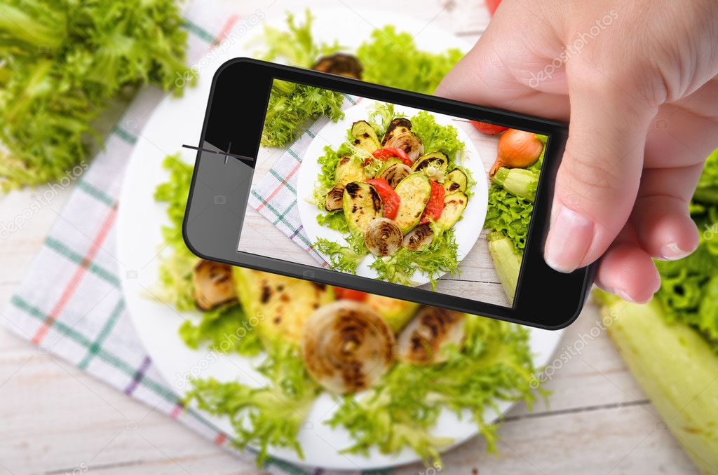 Hands taking photo grilled vegetables with smartphone