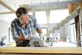 Fotografie muž pomocí elektrické viděl uvnitř domu ve výstavbě