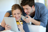 Fotografia giovane coppia a casa comprando su internet