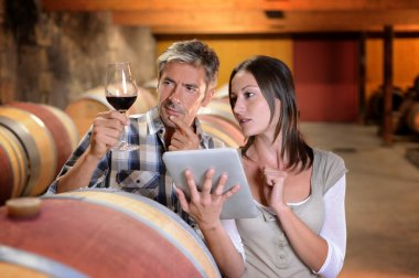 Winemakers in cellar using electronic tablet to control wine quality