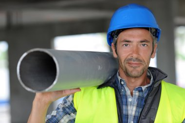 Construction worker on site holding pipe