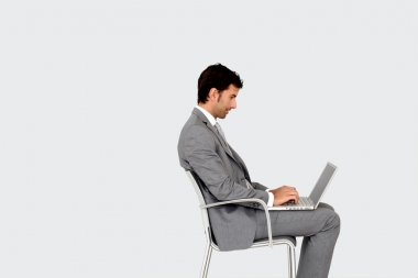 Businessman sitting on chair in front of laptop