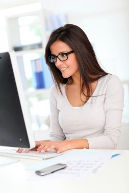 Beautiful office worker in front of desktop computer