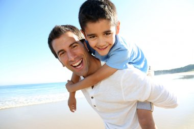 Father holding son on his shoulders at the beach