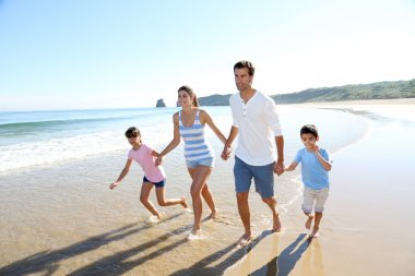 Family having fun running on the beach stock vector