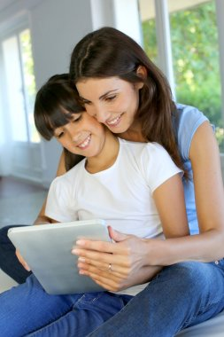 Mother and daughter websurfing on internet with tablet