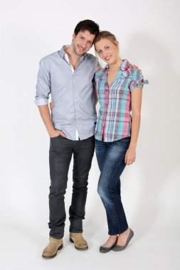 Young cute couple standing on white background