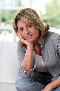 Senior woman at home sitting in sofa stock vector