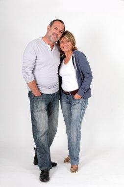 Modern senior couple standing on white background