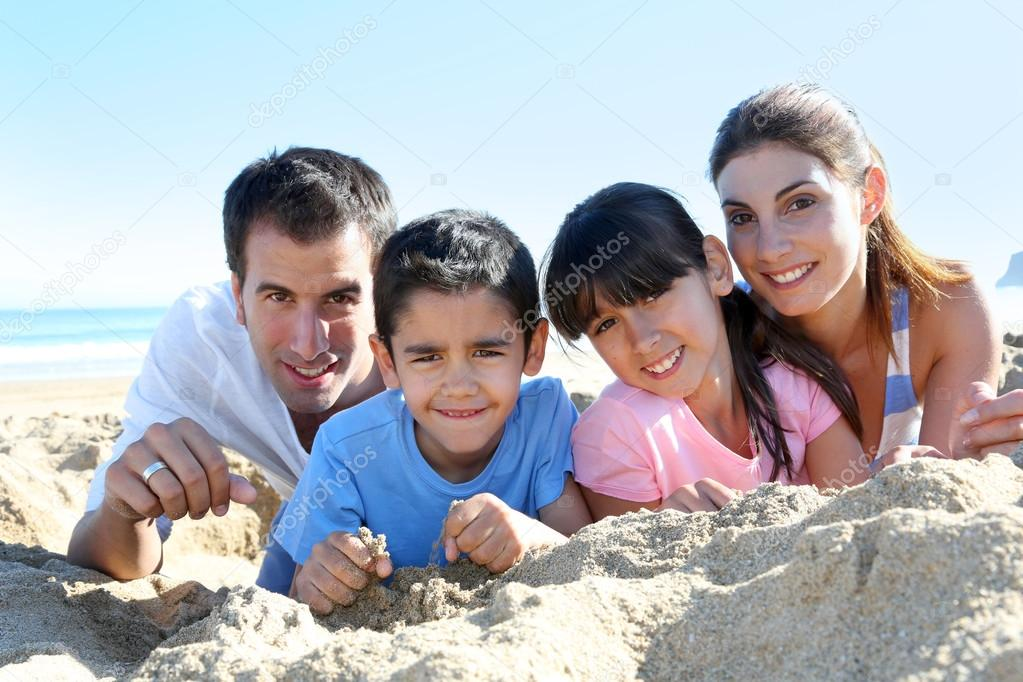 Family of four laying on a sandy beach