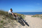 Couple sitting by bicycles on a sand dune