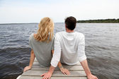 Fotografie Rear view of couple sitting on a wooden bridge by a lake