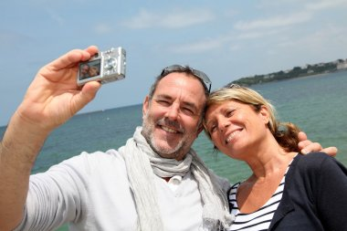 Retired couple taking picture of themselves by the sea