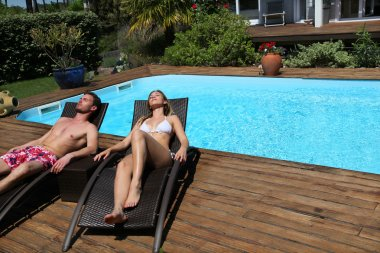 Couple in long chairs by swimming pool