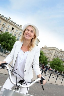 Cheerful middle aged woman riding bike in town
